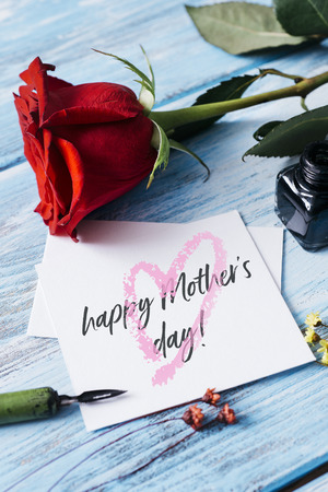 closeup of a red rose, an ink bottle, a nib pen and a piece of paper with the text happy mothers day written in it, on a blue rustic wooden table