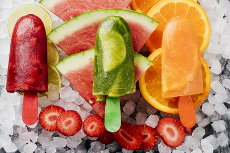 high angle view of some different homemade ice pops, made with different natural fruit juices and pieces of fruit, such as watermelon, strawberry, peach, lime or orange, placed on ice Banque d'images