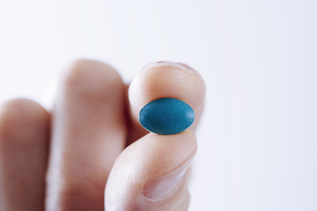 closeup of a young caucasian man with a blue pill in his hand against a white background, with some blank space