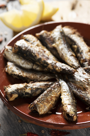 closeup of some spanish grilled sardines in a brown earthenware plate, on a gray rustic wooden table