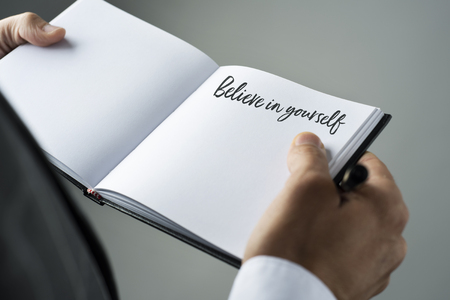closeup of a young caucasian man in an elegant suit with a notebook in his hands with the text believe in yourself written in it Stock fotó