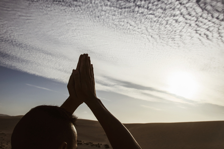 closeup of a young caucasian man practicing yoga outdoors, against a cloudy sky, with the sun in the background