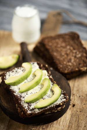 closeup of a slice of rye bread topped with some slices of avocado, and a glass jar of yoghurt, on a rustic wooden table
