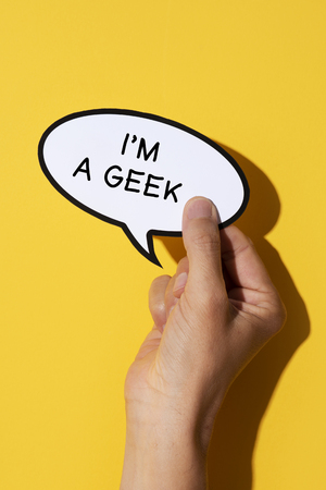closeup of the hand of a young caucasian man with a speech balloon, with the text I am a geek written in it, on a yellow background Imagens