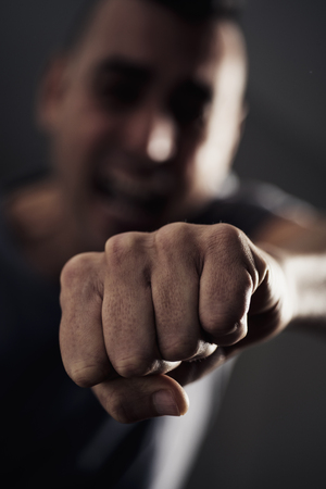 closeup of a young caucasian man throwing a punch to the observer, with a dramatic effect Stock fotó