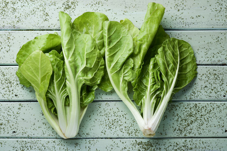 high angle view of some raw chard leaves on a rustic pale green wooden table