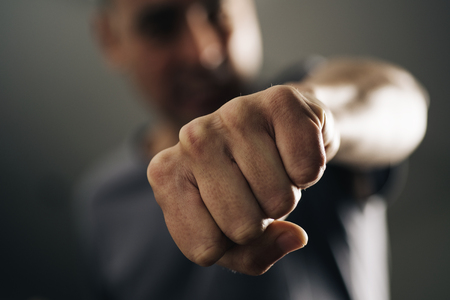 closeup of a young caucasian man throwing a punch to the observer, with a dramatic effect