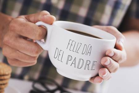 closeup of a caucasian man with a white ceramic cup with coffee in his hands, with the text feliz dia del padre, happy fathers day written in spanish, at a table set for breakfast