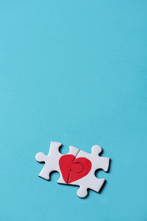 two pieces of a puzzle forming a heart, depicting the idea that love is a matter of two, on a blue background, with some blank space on top