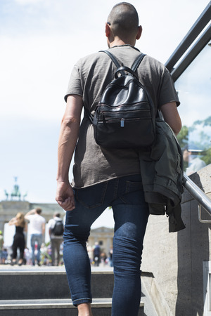 closeup of a young caucasian man, seen from behind, leaving a subway station or an underground parking in Berlin, Germany, in front of the popular Brandenburg Gate in the background