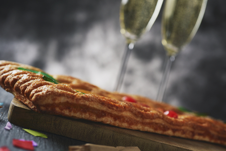 closeup of a coca de Sant Joan, a typical sweet flat cake from Catalonia, Spain, eaten on Saint Johns Eve, on a rustic table, next to a pair of glasses with champagne, firecrackers and confetti