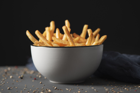 some appetizing french fries served in a white ceramic bowl, placed on a gray rustic wooden table, against a black background