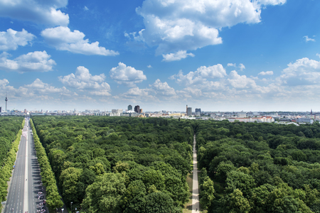 an aerial view of the Tiergarten park in Berlin, Germany, with the skyline of the city in the background, highlighting the Fernsehturm television tower on the left