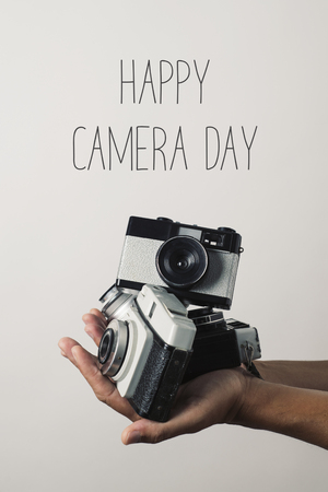 closeup of the hand of a caucasian man holding some retro film cameras and the text happy camera day against an off-white background