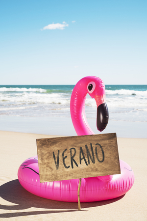 """a rustic signboard with the text """"verano"""", """"summer"""" written in spanish, and a swim ring in the shape of a pink flamingo on the sand of a beach, with the ocean in the background"""
