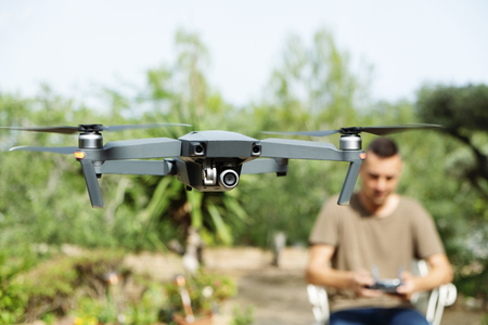closeup of a caucasian man operating a drone, remotely controlled with a smartphone, in a natural landscape