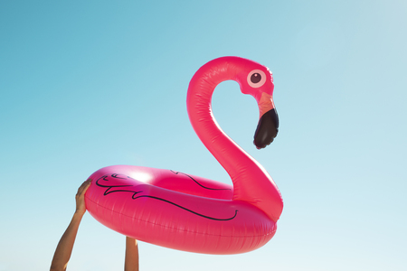 closeup of a young caucasian man with a swim ring in the shape of a pink flamingo in his hands against the sky, with some blank space around it