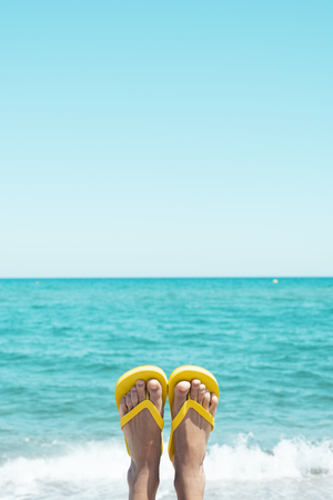 closeup of the legs of a young caucasian man on the beach, upside down, wearing a pair of yellow flip-flops, against the sky with a blank space on top