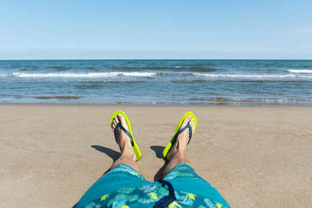 closeup of the legs of a young caucasian man relaxing on the beach, wearing a blue swimsuit and a pair of green flip-flops, with the ocean in the background and some blank space on the sky Stock Photo