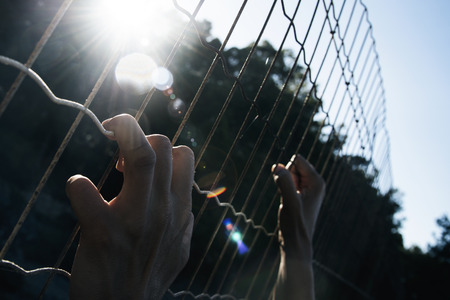 closeup of the hands of a man trying to climb up a metal fence Archivio Fotografico