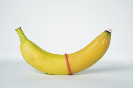 closeup of a banana with a pink condom in it on an off-white background Stock Photo