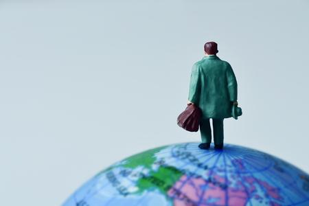 Hombre viajero en miniatura visto desde atrás llevando una maleta, en la parte superior del globo terrestre contra un fondo blanquecino con algún espacio en blanco Foto de archivo