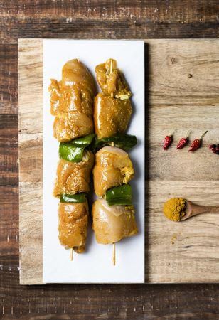 closeup of some raw spiced chicken meat skewers, mixed with green pepper, on a white marble tray, on a wooden table Foto de archivo