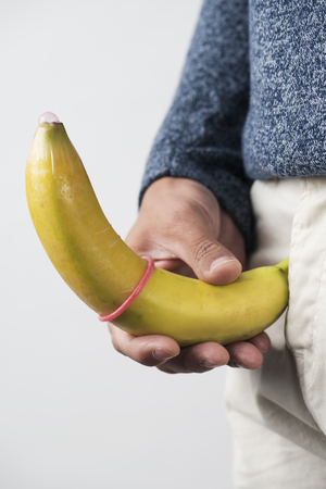 closeup of the a young caucasian man holding a banana with a pink condom in it in front of his crotch Фото со стока