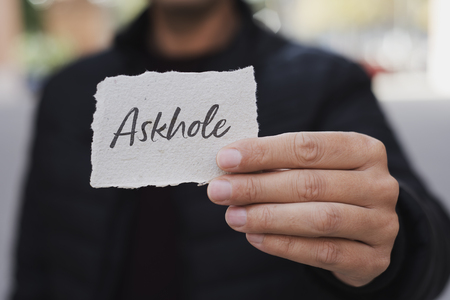 closeup of a young caucasian man, on the street, showing a piece of paper with the word askhole written in it, for the person who constantly asks for advice and does the opposite
