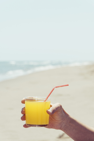closeup of a young caucasian man on the beach, with a glass with a refreshing orange drink in his hand, with the sea in the background and a blank space on top Stock Photo
