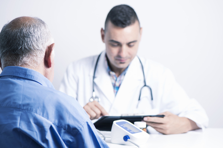 closeup of a senior caucasian patient man seen from behind and a caucasian doctor man checking his medical history or the results of a test in his tablet, sitting both at the doctors desk