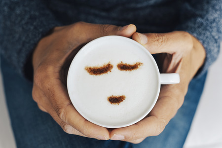 high angle view of a young caucasian man having a cup of cappuccino in his hands, with a happy face drawn with cocoa powder on its milk foam