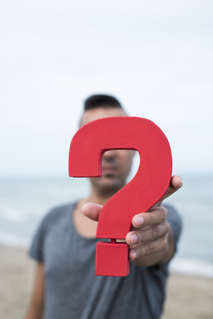 closeup of a young caucasian person with a question mark in front of her or his face, with the ocean in the background