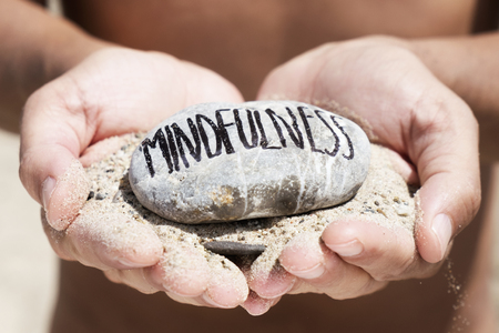 closeup of a young caucasian man, on the beach, with a handful of sand in his hands and a stone on top with the text mindfulness written in it