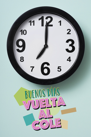 closeup of a clock and the text good morning, back to school written in spanish on a green background