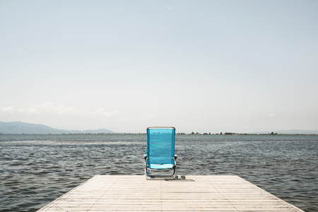 a blue deck chair at the end of a wooden pier next to the water, with a blank space on the clear sky