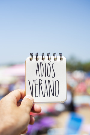 closeup of the hand of a young caucasian man in the seashore of a beach showing a spiral notepad with the text adios verano, good bye summer in spanish, handwritten in it