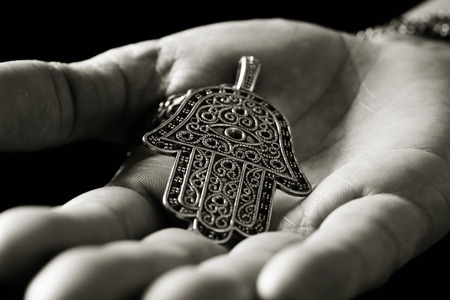 closeup of an old hamsa amulet, also known of the hand of fatima or the hand of mary, on the palm of the hand of a young man, in black and white