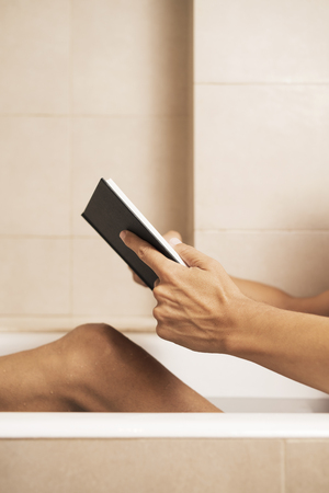 closeup of a young caucasian man reading a book while is taking a bath in the bathtub of a beige bathroom Imagens