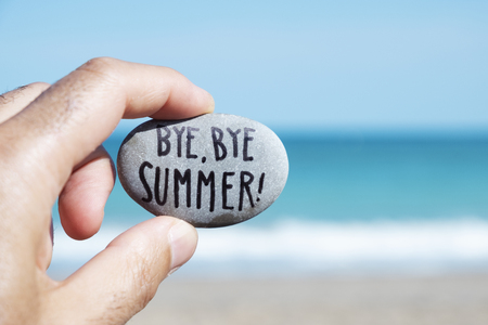 closeup of the hand of a young caucasian man on the beach, in front of the ocean, holding a stone with the text bye, bye summer written in it