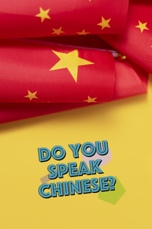 some flags of China and the question do you speak Chinese? on a yellow background