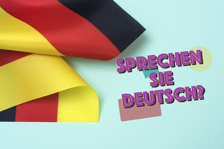 some flags of Germany and the question sprechen sie deutsch? do you speak German? written in German, on a green background Archivio Fotografico