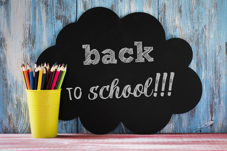 a pencil pot with pencil crayons of different colors on a red rustic surface, and the text back to school written in a black thought bubble, against a blue rustic wooden background