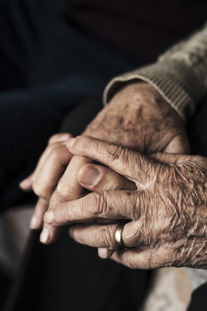 closeup of a young caucasian man holding the hand of an old caucasian woman, with their fingers entwined with affection 版權商用圖片