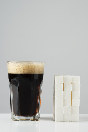 a glass of cola drink and a pile of white sugar cubes, disposed in a block, on an off-white background with some blank space on top, depicting the high sugar content of this kind of drinks Archivio Fotografico