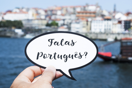 the hand of a young caucasian man holding a speech bubble with the question falas portugues, do you speak Portuguese? written in Portuguese, in Porto, Portugal, with the Douro River in the foreground
