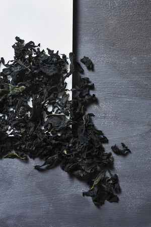high angle view of a pile of dried leaves of wakame, an Asian edible seaweed used in traditional soups such as the miso soup, on a white plate, placed on a gray rustic table