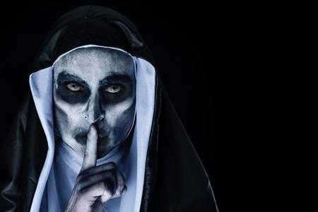 Primer plano de una aterradora monja malvada, vistiendo un típico hábito blanco y negro, pidiendo silencio, sobre un fondo negro con un espacio en blanco a la derecha Foto de archivo