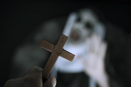 Gros plan d'une croix dans la main d'un homme et d'une nonne maléfique effrayante, portant une habitude typique en noir et blanc, hurlant Banque d'images