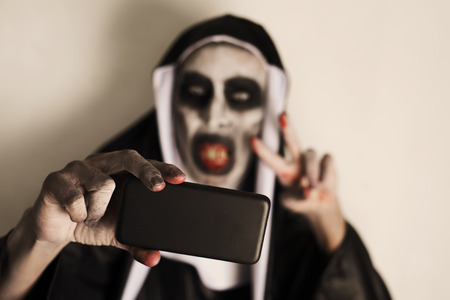 closeup of a frightening evil nun, wearing a typical black and white habit, taking a selfie with a smartphone while giving a V sign